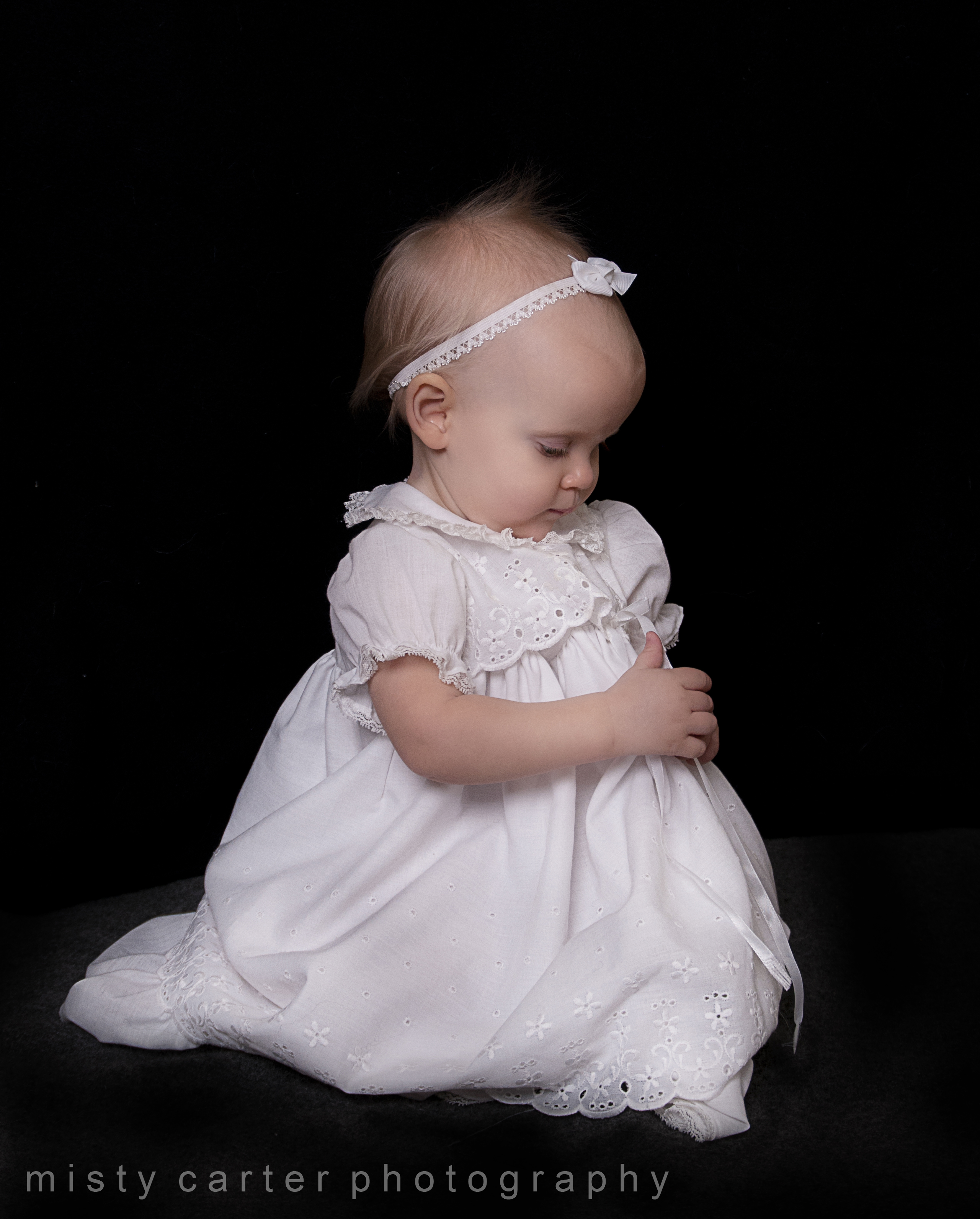 Baby girl in Christening baptism gown on black background praying