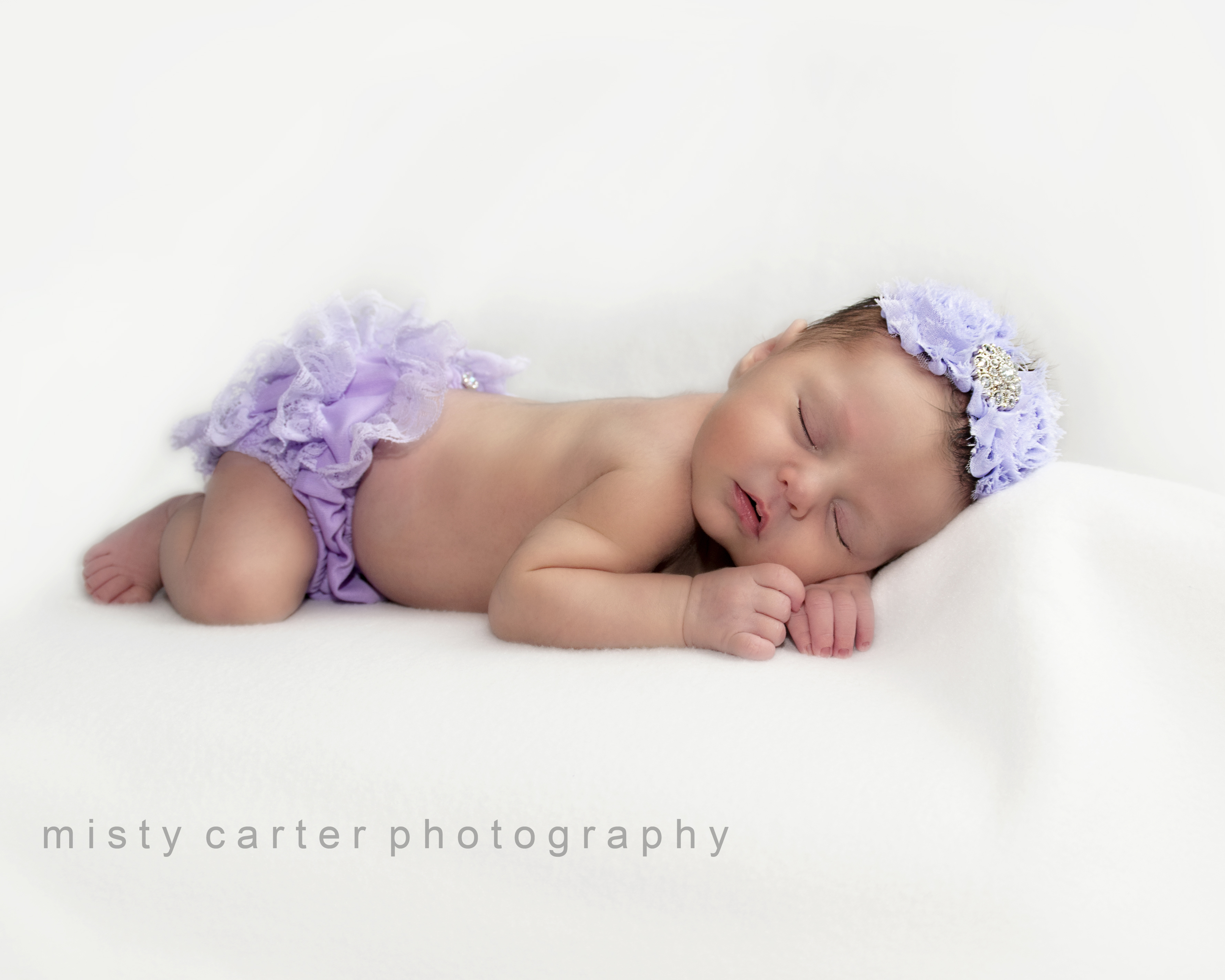 """""""This is my favorite image, my newborn baby girl all curled up on her belly. She was really fussy at the beginning of our photo shoot, but Misty was so patient and soothing that she eventually calmed down and gave us beautiful pictures. As a new mom, I was stressed before the photo shoot and just wanted my baby to cooperate. Misty was such a calming presence and took all the pressure off me. I will cherish the pictures we got that day forever."""""""