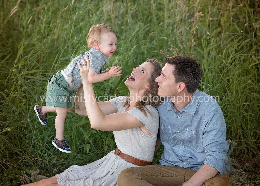 parents laughing and playing with young son in candid lifestyle family pictures