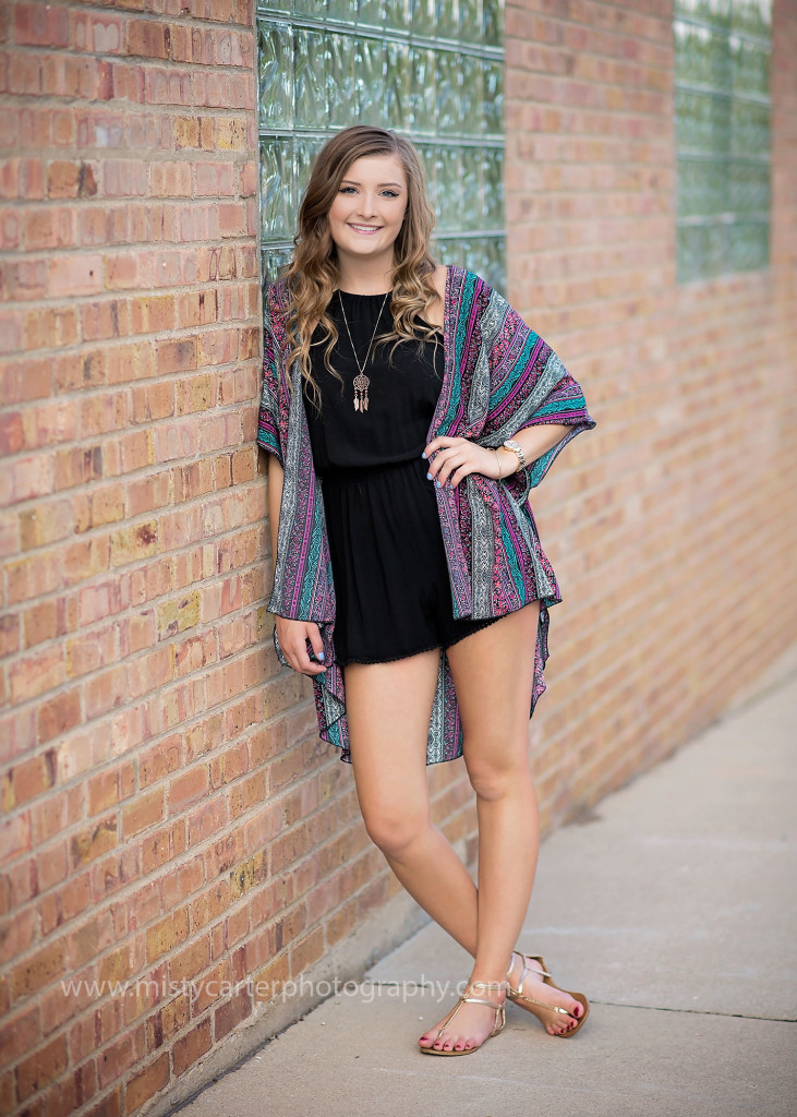 girl in layered clothing for senior pictures leaning on brick wall