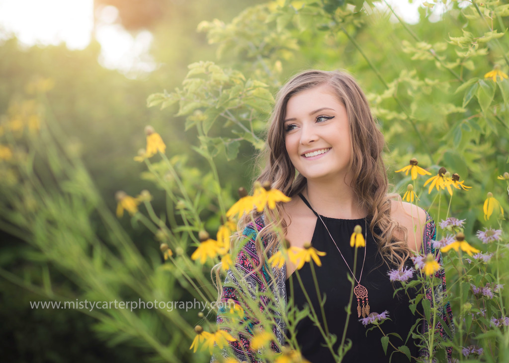 girl in wild flowers at sunset for senior pictures