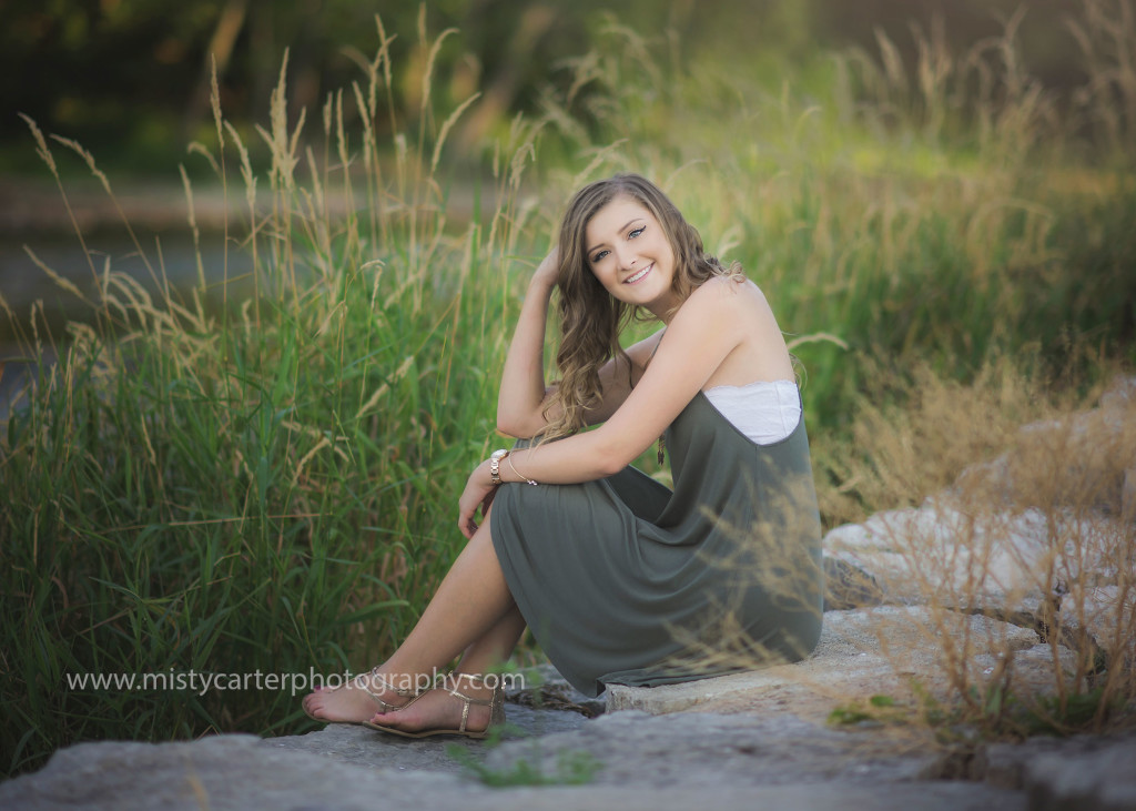senior sitting on river bank surrounded by tall grasses