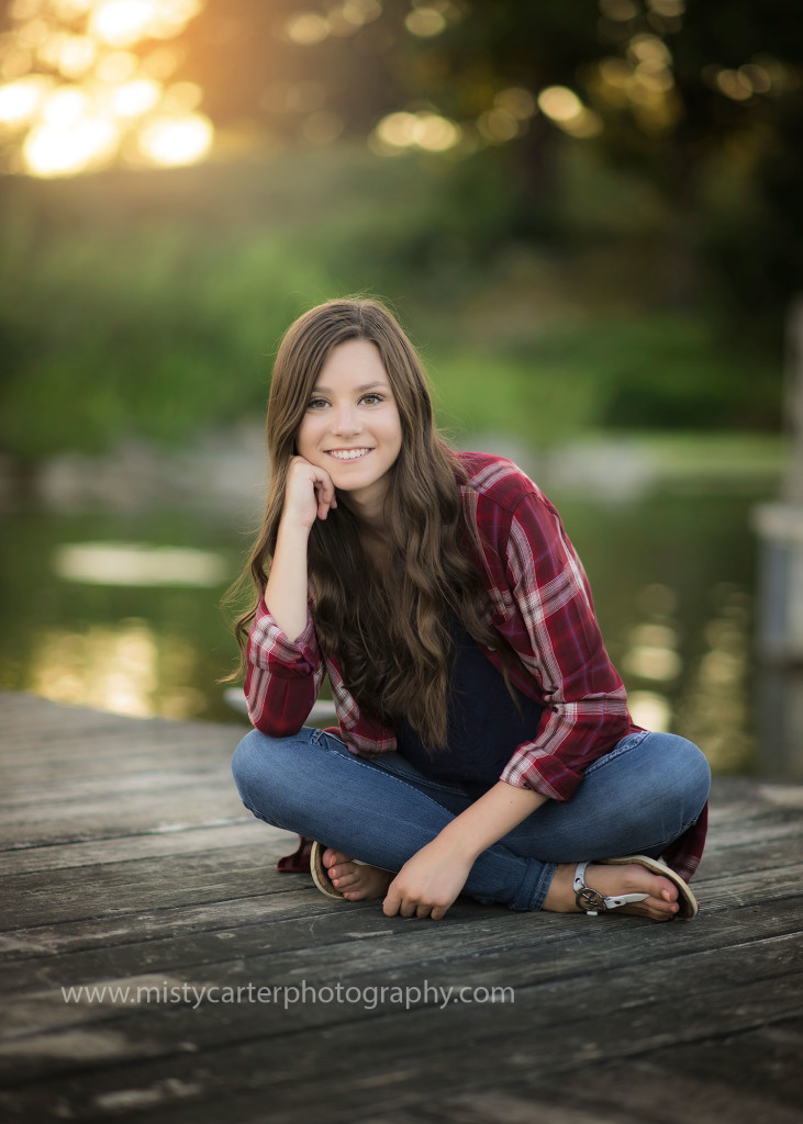 girl in plaid shirt sitting on a dock by the water at sunset