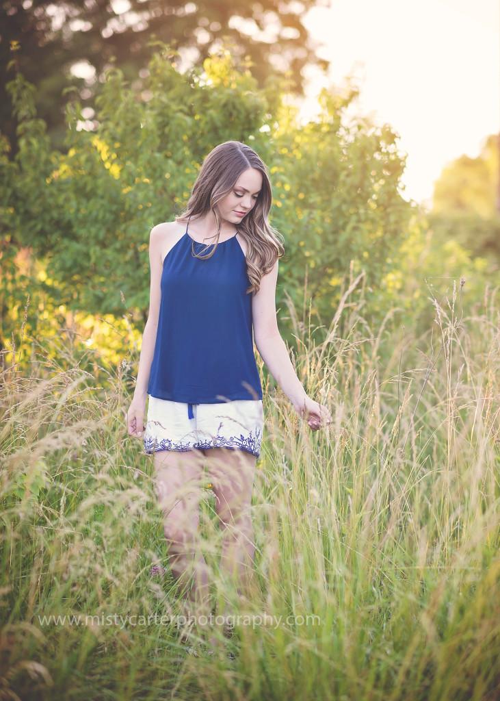 girl brushing tall grasses