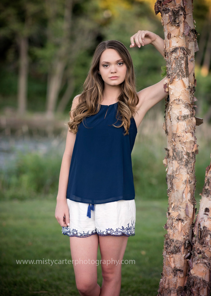 girl leaning on birch tree