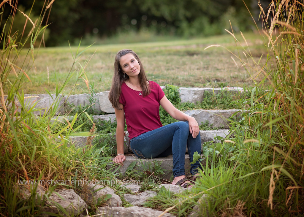 high school senior girl on rock steps by river bank
