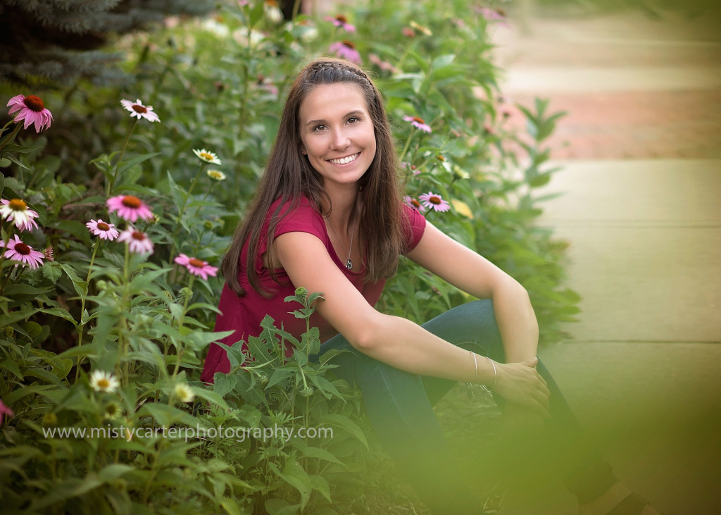 artistic high school senior pictures with girl framed by flowers and foreground bokeh