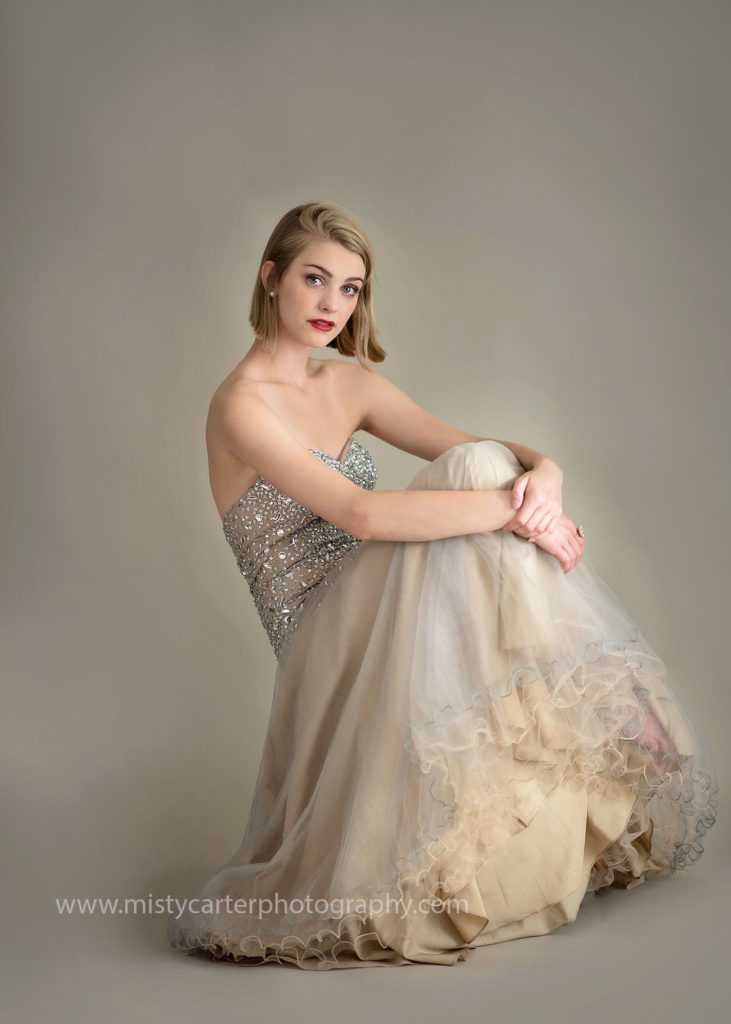 girl in photography studio in prom dress for senior pictures