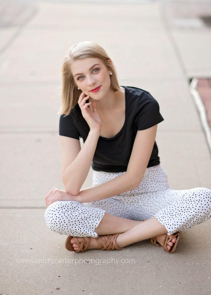 girl sitting on urban sidewalk for senior pictures