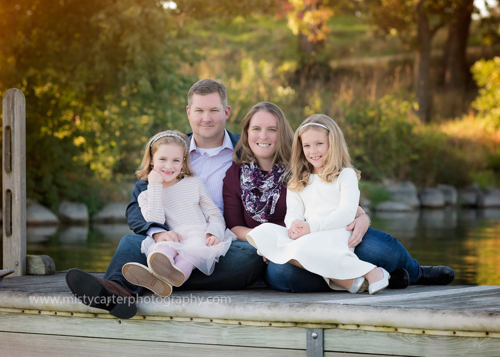 family sitting snuggled close on dock by river