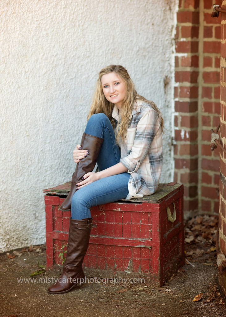 girl in riding boots and flannel shirt posing at horse barn for senior pictures