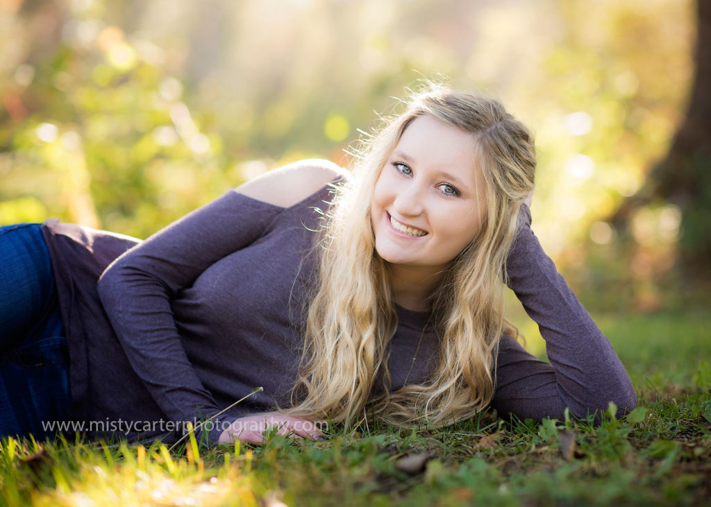girl lying in grass with golden sunshine in her hair for casual natural senior portraits