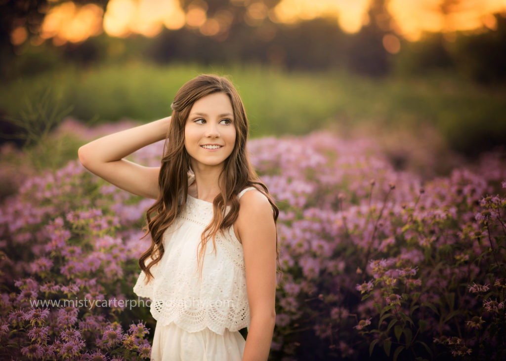 beautiful girl surrounded by purple flowers at sunset