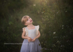 whimsical portrait of girl with floating seed