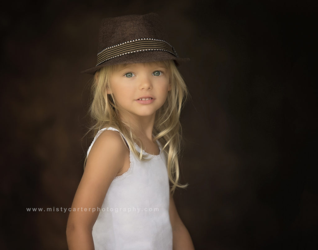 young girl in formal portrait wearing hat