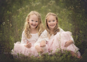 sisters in pale dresses sitting in wildflowers photography