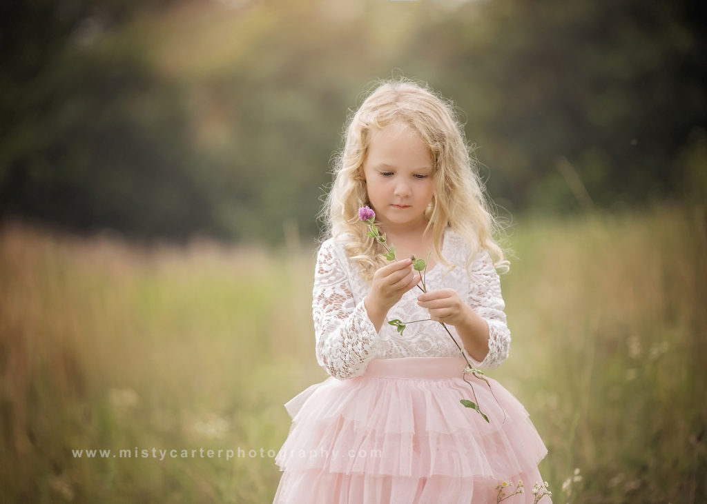 little girl looking at clover flower