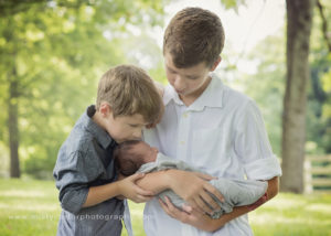 brothers holding newborn baby