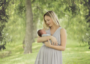 beautiful mom with newborn baby girl in park